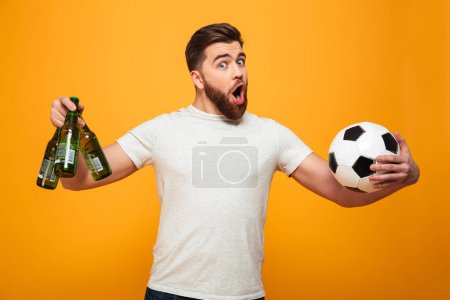 Portrait of an excited bearded man holding football