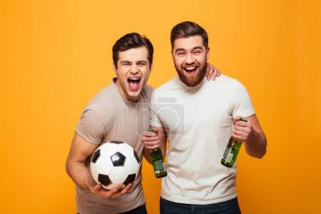 Portrait of a two cheerful young men holding beer bottles