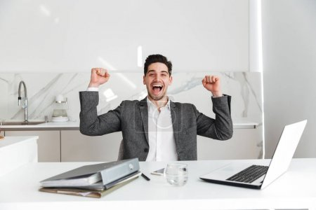 Horizontal portrait of happy unshaved man in suit screaming and