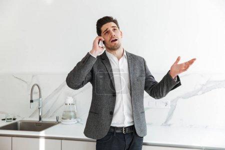 Portrait of serious businesslike man negotiating on mobile phone