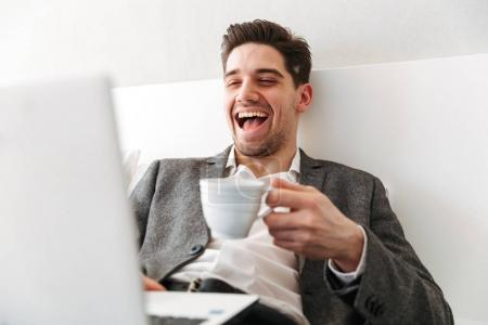 Photo of happy man in businesslike clothes bursting into laughte