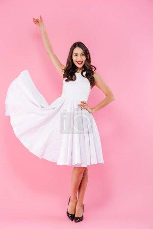 Photo pour Portrait de toute la longueur d'une jeune femme asiatique heureuse habillée en robe blanche, posant en position debout isolé sur fond rose - image libre de droit