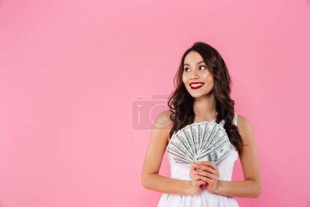 Image of happy rich asian woman holding fan of money in dollar c