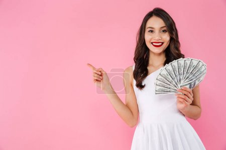 Image of successful asian woman 20s holding fan of money in doll