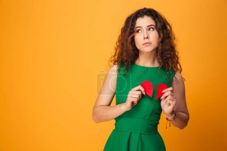 Sad young lady holding broken heart.