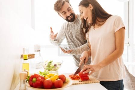 Portrait of an excited young couple cooking salad together