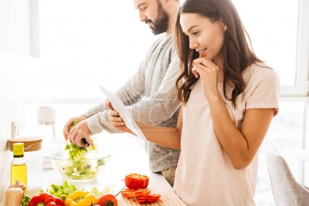 Portrait of a happy young couple cooking salad