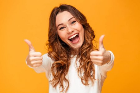 Happy brunette woman in sweater showing thumbs up