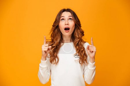 Photo for Image of beautiful cute young woman standing isolated over yellow background pointing. Looking aside. - Royalty Free Image