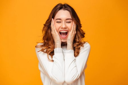 Photo for Image of excited screaming young woman standing isolated over yellow background. - Royalty Free Image
