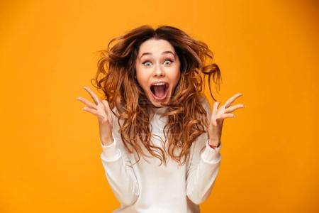 Photo for Image of excited screaming young woman standing isolated over yellow background. Looking camera. - Royalty Free Image
