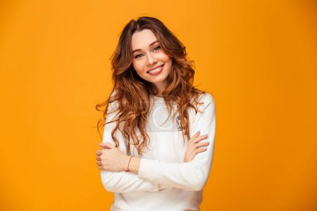 Smiling brunette woman in sweater posing with crossed arms