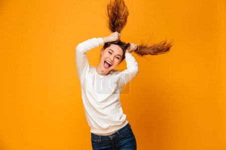 Laughing brunette woman in sweater holding her hair