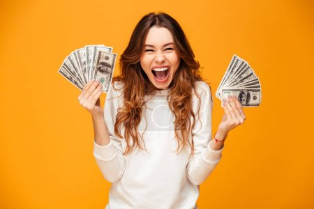 Photo for Happy screaming brunette woman in sweater holding money and rejoices while looking at the camera over yellow background - Royalty Free Image