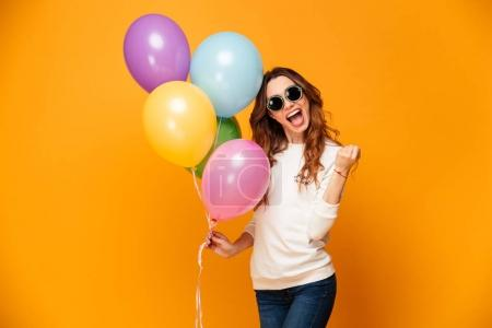 Happy screaming brunette woman in sweater and sunglasses holding balloons