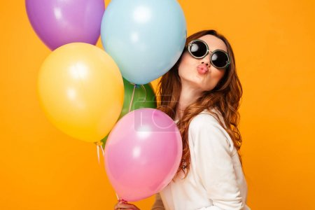 Pleased brunette woman in sweater and sunglasses holding balloons