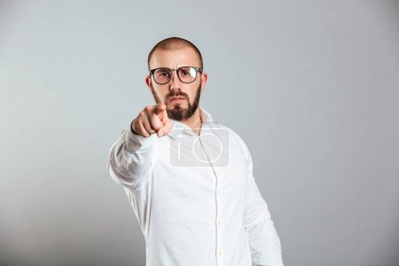 Photo pour Photo de l'homme barbu persistant en chemise blanche et lunettes gestuelle sur l'index de la caméra signifiant hey vous isolé sur fond gris - image libre de droit
