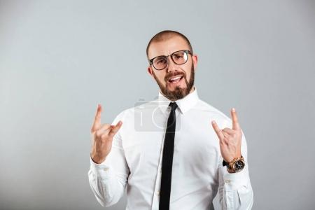 Image of cheerful guy in office outfit smiling and showing rock
