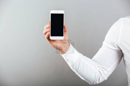 Photo for Close up of man's hand showing blank screen mobile phone isolated over gray background - Royalty Free Image