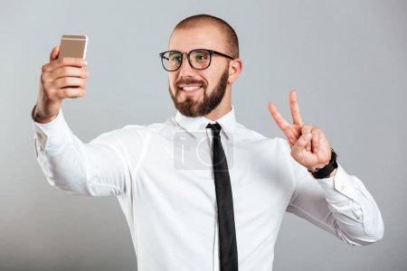 Successful mature man in glasses and tie showing peace sign whil