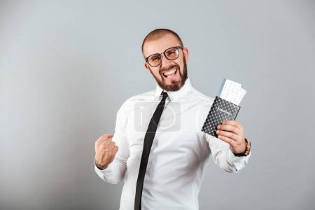 Photo of delighted businessman rejoicing his vacation while hold
