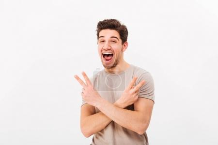 Portrait of cool guy showing victory sign with two hands and exp