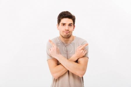 Image of indecisive man wearing beige t-shirt gesturing fingers