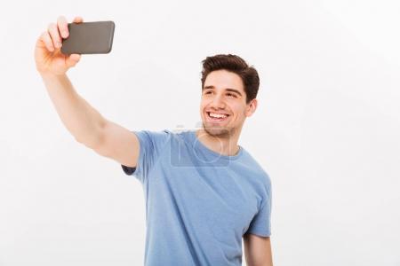 Joyful man with brown hair smiling on camera while taking selfie