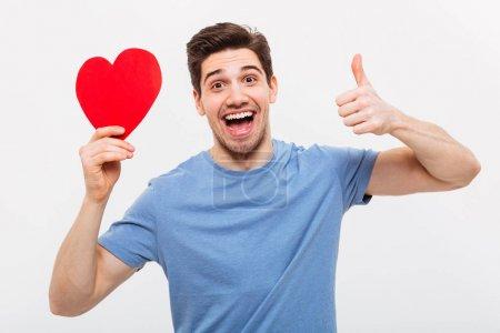 Photo pour Homme joyeux en t-shirt tenant coeur en papier et montrant pouce vers le haut tout en regardant la caméra sur fond gris - image libre de droit
