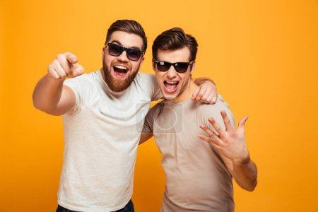 Two happy men friends in casual t-shirts and sunglasses having f