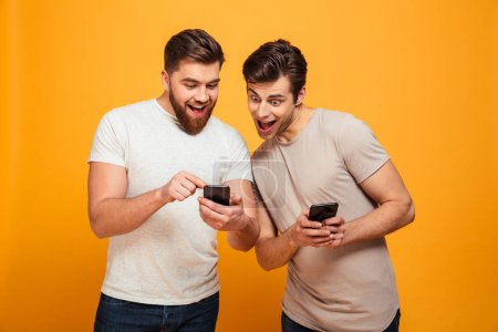 Photo pour Deux hommes joyeux dans la conversation occasionnelle et en regardant les téléphones mobiles dans leurs mains isolés sur fond jaune - image libre de droit