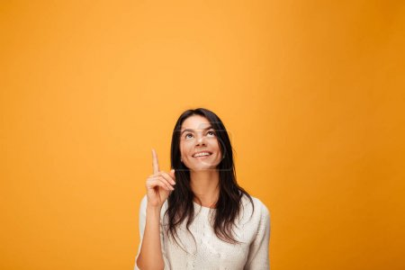 Portrait of a happy young woman pointing finger up