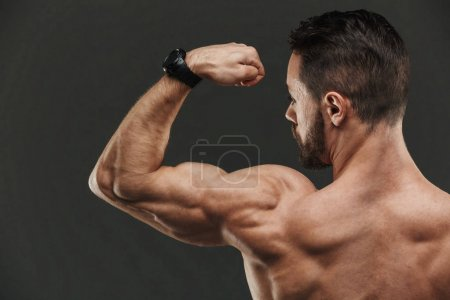 Close up of a muscular bodybuilder flexing biceps