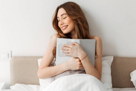 Portrait of beautiful smiling woman resting in comfortable bed a
