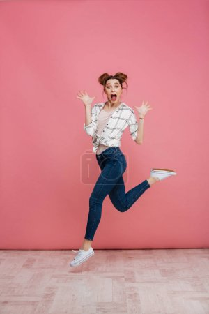 Photo for Full length portrait of an excited young girl celebrating success while jumping isolated over pink background - Royalty Free Image
