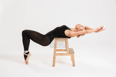 Photo pour Photo d'une belle jeune fille ballerine sur tabouret sur fond blanc mur isolé . - image libre de droit