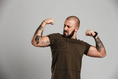Photo of strong tattooed guy with beard and mustache showing his