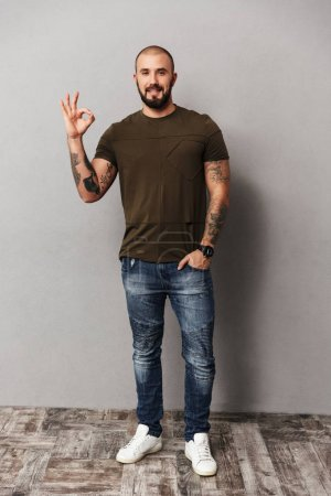Full-length image of unshaved baldy guy wearing casual looking a