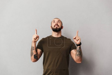 Photo for Image of bearded man with tattoos on arms looking upward with pointing fingers on copyspace isolated over gray background - Royalty Free Image
