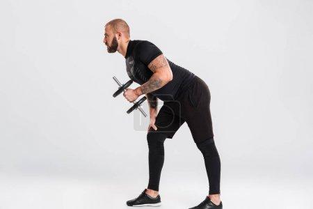 Profile of young sportsman bodybuilder in black sportswear train