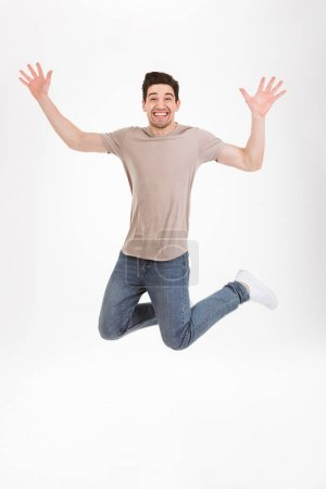 Full-length photo of excited man 30s in casual t-shirt and jeans