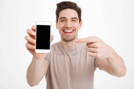 Young man in casual t-shirt demonstrating mobile phone and point