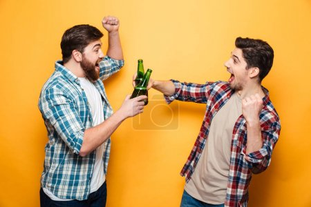 Portrait of a two happy young men toasting with beer
