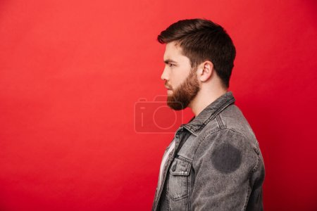 Portrait in profile of concentrated bearded man in jeans jacket