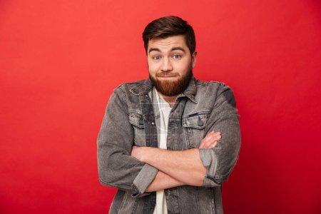 Foto de Foto de hombre con barba en la chaqueta de jeans encogiéndose y no expresar ninguna idea estando con los brazos cruzados aislados sobre fondo rojo - Imagen libre de derechos