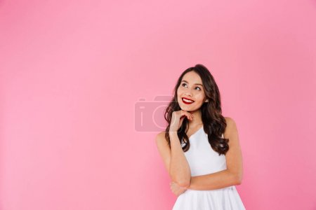 Photo for Portrait of gorgeous asian woman 20s with dark long hair in white dress smiling and looking upward on copyspace isolated over pink background - Royalty Free Image