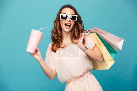 Photo for Portrait of a happy beautiful girl wearing dress and sunglasses holding shopping bags and soda water cup isolated over blue background - Royalty Free Image
