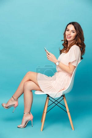 Photo pour Portrait d'une belle fille souriante portant une robe tenant un téléphone portable assis sur une chaise isolée sur fond bleu - image libre de droit