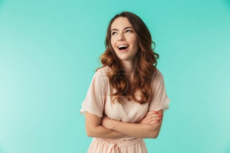 Photo for Portrait of a laughing young girl in dress standing with arms folded and looking away isolated over blue background - Royalty Free Image