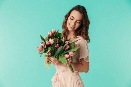 Photo for Portrait of a satisfied young girl in dress holding pink tulips bouquet isolated over blue background - Royalty Free Image